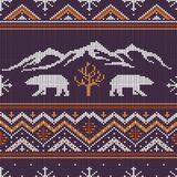 Winter knitted woolen pattern with polar bears. On a background of snow-capped mountains Stock Image