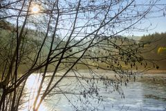 Winter kommt: Nachmittagssonne über kleinem gefrorenem See in Hessen Deutschland stockbild