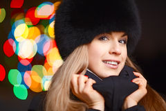 Winter Lady. Night winter portrait of a pretty young lady with a Christmas tree lights on background - shallow DOF, focus on eyes Stock Images