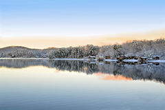 Winter on the Lake. A beautiful wintry early morning lake landscape with homes, snow, lake, mountains, and reflections Royalty Free Stock Photos