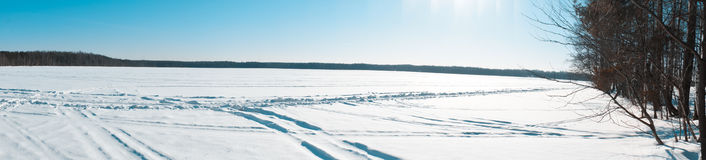 Panoramic view of winter lake. Winter lake covered by white snow with ski trace under a blue sky Stock Photography