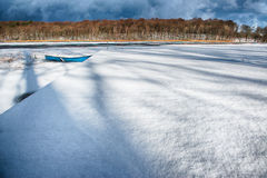 Winter lake. Dark clouds over a frozen lakewith a forgotten rowboat stock photos