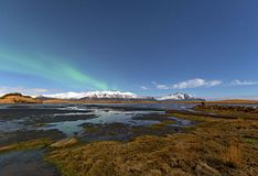 Winter lake near mountain in Hofn, Iceland. Northern lights and royalty free stock images