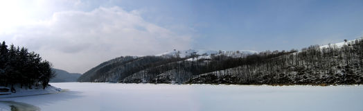 Winter lake panorama. Secu lake in Semenic Mountains - Romania. Wide view of the fronzen lake during winter Royalty Free Stock Photo