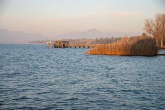 A winter lake with the sky with clouds in the warm evening light. Reeds on the shore. Pier with wooden structure. Background mountains profile royalty free stock photography