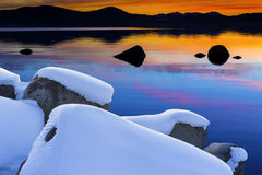 Winter Lake Tahoe Scenic at Sunset. Snow covered boulders in the clean clear waters of Lake Tahoe in Winter with vivid sunset and reflections Royalty Free Stock Image