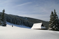 Winter landscape. Wooden cabin in the mountains covered by snow Royalty Free Stock Photography