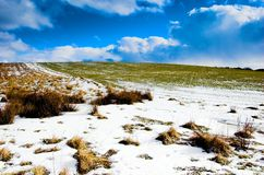 Winter landscape. Winter - spring sunny meadow with snow, blue sky and clouds stock image