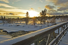 Winter Landscape. Snow covered bridge over icy river at sunset Stock Images