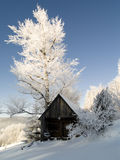 Winter landscape. Small wooden cottage. Blue sky and a lot of white snow Stock Photos