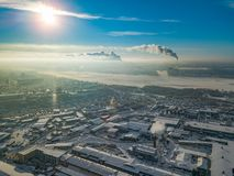 Winter landscape from a aerial view of the city of Novosibirsk in the haze with streets, small buildings, river under ice covered stock photo