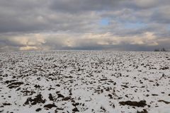 Winter landscape - arable land covered with the first fallen snow on a clear day Stock Photography