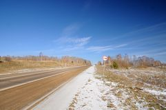 Winter landscape with asphalt road, bare trees, first snow and no overtaking road sign under dark blue sky stock images