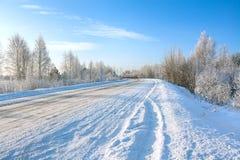 Winter landscape with asphalt road,forest and blue sky. Stock Image