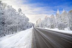 Winter landscape with asphalt road,forest and blue sky Royalty Free Stock Photography