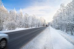 Winter landscape with asphalt road,forest and blue sky. Royalty Free Stock Photo
