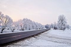 Winter landscape. Asphalted rural road at an early, cold winter sunrise - image royalty free stock image
