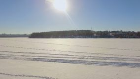 Winter landscape. Beautiful view of the winter city and the lake from a bird`s-eye view. Camera is flying low over the surface of the frozen lake stock video footage