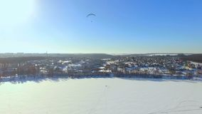 Winter landscape. Beautiful view of the winter city and the lake from a bird`s-eye view. paraglider is flying over a. Frozen lake. Ternopil Ukraine stock video footage