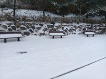 Winter landscape bench in the snow. Winter landscape bench covered with snow in snowfall winter season Royalty Free Stock Image