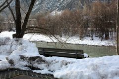 Winter landscape with bench on the river coast in Alps in Austria.  Royalty Free Stock Image