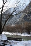 Winter landscape with bench on the river coast in Alps in Austria.  Royalty Free Stock Photos