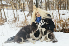 Winter landscape with blonde girl playing with siberian husky malamute dogs outside. Forest, beach, frozen river Stock Image