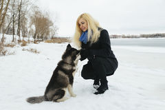 Winter landscape with blonde girl playing with siberian husky malamute dogs outside. Forest, beach, frozen river Stock Photo