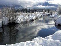 Winter landscape with blue sky reflecting in a riv. Er near Whistler Stock Photo
