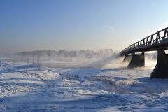 Winter landscape with bridge. The river does not freeze. And above it rises the steam Royalty Free Stock Photos