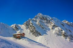 Winter landscape with cabin at Balea Lake and Fagaras. Alpine winter landscape with cabin at Balea Lake and Fagaras Mountains covered with snow in Sibiu County Royalty Free Stock Images