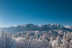 Winter landscape of carpathians mountains. Snowy fir-trees, blue and clear sky after sunrise. Romania, Poiana Brasov. Stock Photo