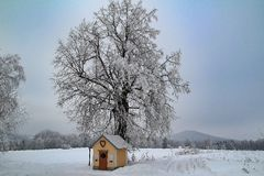 Winter landscape with cloudy sky. And chapel in foreground Royalty Free Stock Photos