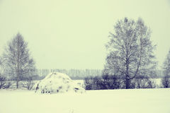 Winter landscape in a cold dull day with haystack Stock Photos