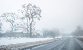 Winter landscape of a countryside road with houses Stock Photography