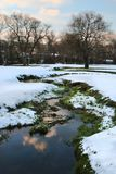 Winter landscape of creek winding through snow-covered meadow Stock Image