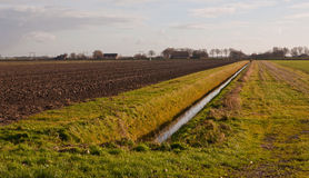 Winter landscape with a ditch and a plowed field Stock Image