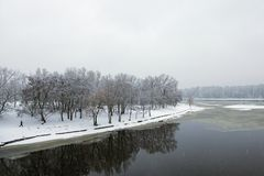 Winter landscape of the Dnipro River and park at the bank. Snow covers tree`s brunches and ground. Kyiv, Ukraine Stock Photo