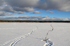 Winter landscape with a drill for ice on a frozen lake in the woods. Winter fishing. Royalty Free Stock Photos