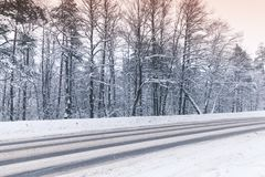 Winter landscape with an empty highway. Going through the forest stock photos