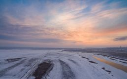 Winter landscape evening sunset over snowy field and river Stock Images
