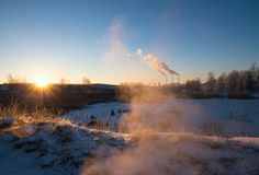 Winter landscape with factory chimneys and clouds against the sun Royalty Free Stock Images
