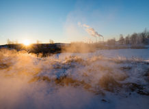 Winter landscape with factory chimneys and clouds against the sun Stock Photos