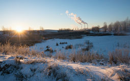 Winter landscape with factory chimneys and clouds against the sun Stock Image