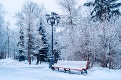 Winter landscape with falling snowflakes- bench covered with snow among snowy winter trees. Winter landscape with falling snowflakes - bench covered with snow stock image