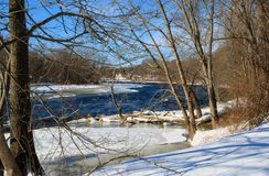 Trees on the banks of the Farmington River. Winter landscape featuring trees lining the banks of an icy Farmington River Royalty Free Stock Image