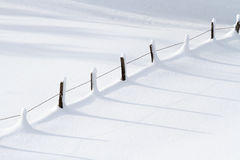 Winter landscape with fence. Deep snow landscape against sun with fence and shadows Stock Photo
