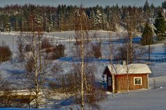 Sunny landscape on very cold winter day. Winter landscape from Finland with old wooden cottage. A lot of snow and freezing temperatures in spite of sun royalty free stock photo