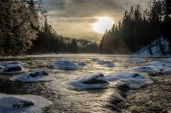 Winter landscape in Finland. View at dawn over river with snow and ice covered rocks and forest of fir trees on both river banks Royalty Free Stock Image