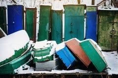 Winter landscape with fisherman boats lying on frozen lake shore Royalty Free Stock Photo